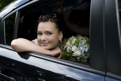 Bride with bouquet sitting in wedding car Stock Images