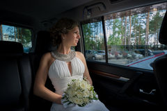Bride with bouquet sitting in wedding car Royalty Free Stock Images
