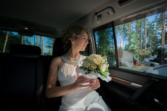 Bride with bouquet sitting in wedding car Stock Photography