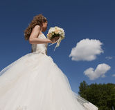 The bride with a bouquet and the sky. Stock Photo