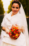 Bride with bouquet in white fur stole Stock Photos