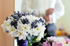 Bride Bouquet. White and lavender flowers bouquet with groom preparing for ceremony Royalty Free Stock Images