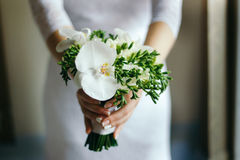 Bride with a bouquet of white Orchid in the hands. Bride with a bouquet of white Orchid in hand decorated with white ribbon Royalty Free Stock Images