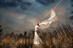 Bride with a bouquest in windy garden stock images