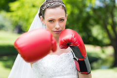 Bride with boxing gloves punching in park Stock Photos