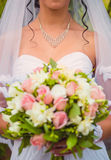 Bride with a bracelet around neck holding flowers Stock Photography