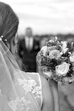 Bride with bridal bouquet in the hands of the groom expect. Royalty Free Stock Photography