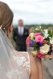 Bride with bridal bouquet in the hands of the groom expect. Royalty Free Stock Photos