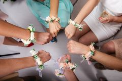 The bride and bride`s maidens are sitting in a circle and holding their fists. Hands with flower bracelets. royalty free stock images