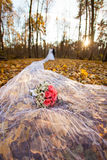 Bride and bridegroom in the autumn forest and bridal bouquet on a long bridal veil Stock Photo