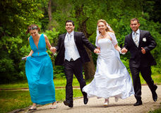 Bride and bridegroom con frainds. Happy bride and bridegroom con frainds running along the alley in the park stock photos