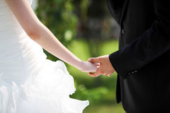 Bride and bridegroom hand in hand. At wedding stock image