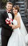 Bride and bridegroom holding bouquet and smiling Stock Photography