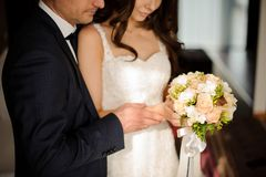 Bride and bridegroom looking together at the bouquet of roses. Beautiful brunette bride in white classic dress and stylish bridegroom looking together at the stock images