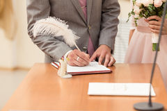 Bride and bridegroom signing the marriage contract after the wedding ceremony Stock Photos