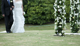 Bride and bridegroom walking for flower door Royalty Free Stock Photography