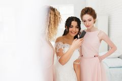 Bride and bridesmaid discussing photos on smartphone. Morning preparation stock photo