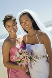Bride And Bridesmaid With Flower Bouquet Smiling On Beach Stock Images