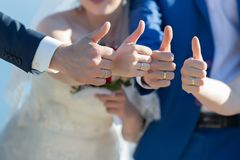 Bride, bridesmaid, groom and groomsman showing thumb up outdoors Stock Photo
