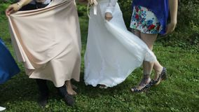 Bride and bridesmaid are holding bouquets of flowers in hands. Bridesmaid are on background. stock footage