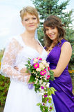 Bride and bridesmaid hugging Stock Photo