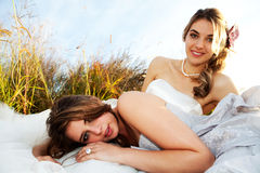 Bride And Bridesmaid Lying in the Grass Royalty Free Stock Photos