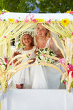 Bride And Bridesmaid Sitting Under Decorated Canopy Stock Photos