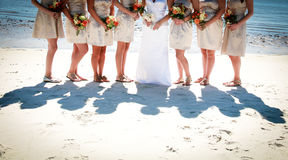 Bride and Bridesmaids. And their shadows at the beach stock photo