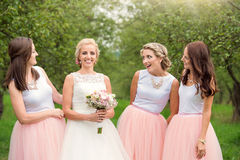 Bride with bridesmaids. Beautiful young bride with her bridesmaids outside in nature royalty free stock photography