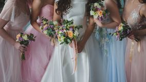 Bride and bridesmaids. Beautiful young women in dresses. And with bouquets of fresh flowers royalty free stock images