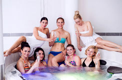Bride and bridesmaids celebrating hen party in wellness center. Cheerful bride and happy bridesmaids in bikinis celebrating hen party in jacuzzi in wellness royalty free stock images