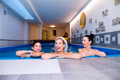 Bride and bridesmaids celebrating hen party in wellness center. Cheerful bride and happy bridesmaids in bikinis celebrating hen party in wellness center, in stock image