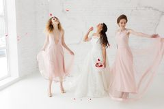 Bride and bridesmaids dancing in white loft studio with flying petals. Full-lenght portrait. Bride and bridesmaids dancing in white studio with flying petals royalty free stock photos