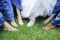 Bride and bridesmaids feet. Bride and bridesmaids showing their feet on green grass Royalty Free Stock Images