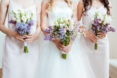 Bride with bridesmaids holding bouquets. Cropped shot of bride with bridesmaids holding bouquets royalty free stock photo