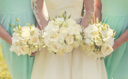 Bride with bridesmaids. Holding wedding bouquets royalty free stock photo