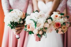 Bride with bridesmaids holding wonderful luxury wedding bouquet of different flowers on the wedding day stock photo