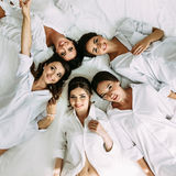 Bride and bridesmaids are lying on the bed. A royalty free stock photo