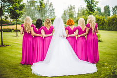 Bride with bridesmaids in a park. On the wedding day stock photo