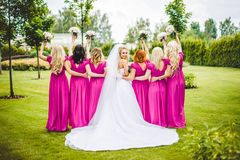 Bride with bridesmaids in a park. On the wedding day stock images