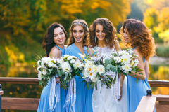 Bride with bridesmaids. In the park on the wedding day stock photos
