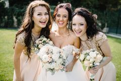 Bride with bridesmaids on the park on the wedding day. Laughing bride and bridesmaids tell funny stories standing on footsteps outside Royalty Free Stock Photo