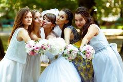 Bride and bridesmaids reach hands with bouquets to the cameraman.  stock images