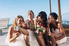 Bride and bridesmaids on rooftop having fun before wedding royalty free stock photo