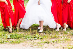 Bride and bridesmaids show off their shoes at wedding. Royalty Free Stock Images