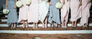 Bride and Bridesmaids Show Shoes. Bride and bridesmaids lined up lifting dresses to show their shoes Royalty Free Stock Photos