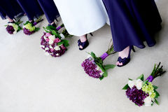 Bride with Bridesmaids Showing off Shoes. A happy bride stands with her bridesmaids Royalty Free Stock Images