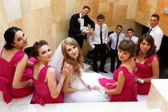 Bride and bridesmaids sit on the white stairs while groom and gr. Oomsmen stand behind stock photo