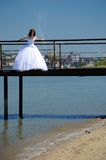Bride on a bridge. Bride on the old bridge looks down royalty free stock photo