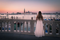 Bride on Bridge at Dawn in Venice. Distant church backlit by red and pink dawn light. A woman dressed in white is seen from behind in this romantic view in Royalty Free Stock Image